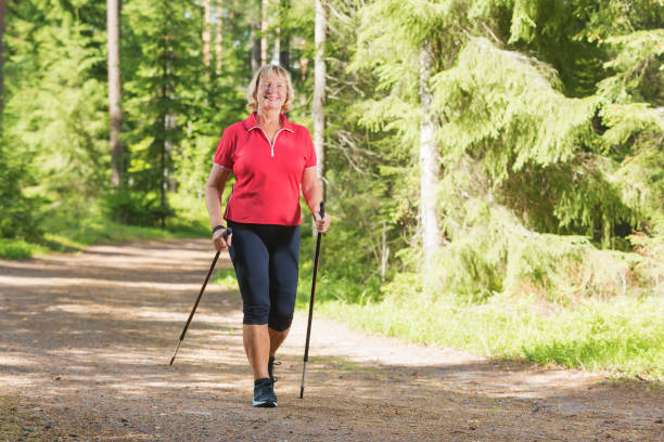 Active senior woman doing nordic walk exercise Nordic walking active senior woman working out in the forest and enjoying beautiful summer day. nordic walking stock pictures, royalty-free photos & images