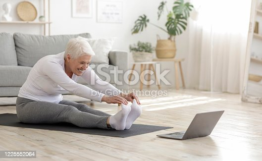 Home Sport. Active Senior Woman Doing Warming Stretching Exercises In Front Of Laptop, Training With Online Tutorials