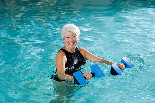 Active donna anziana facendo acqua aerobica - foto stock