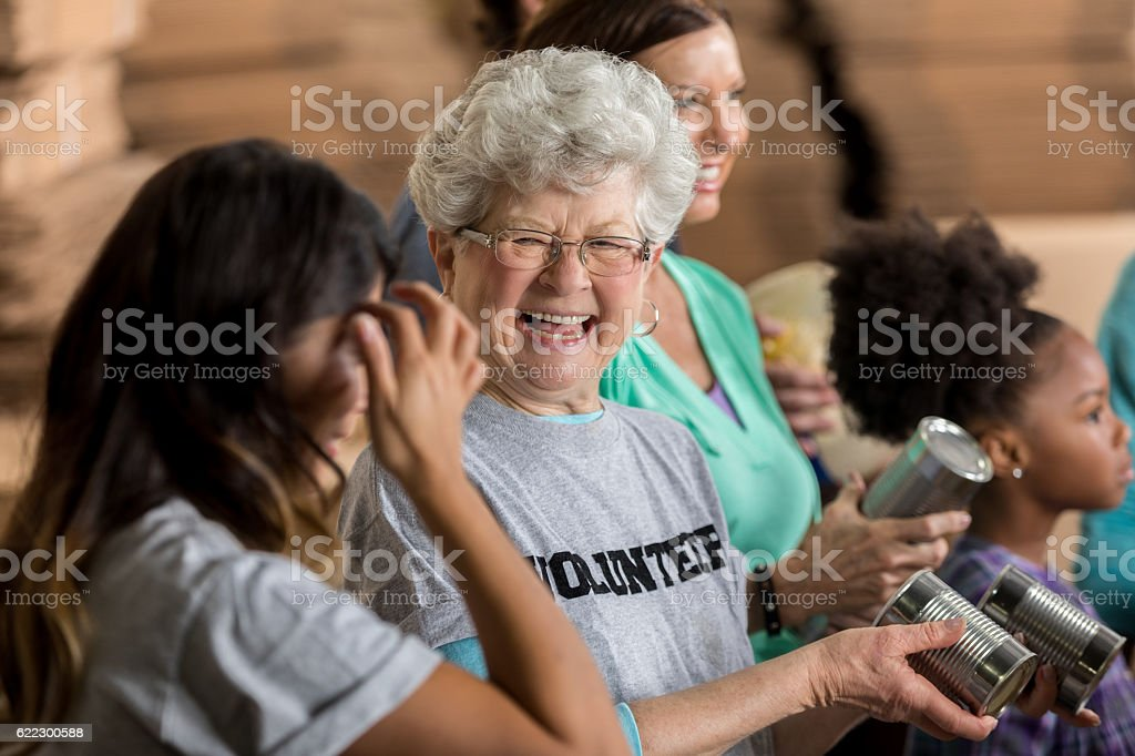 Active senior woman enjoys volunteering at food bank stock photo