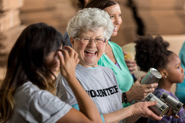active senior woman enjoys volunteering at food bank - volunteer stock photos and pictures