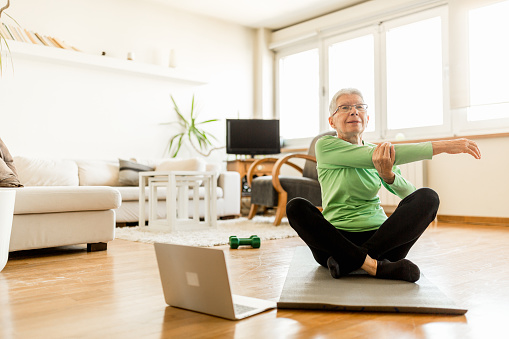 Active senior woman home exercising with online coach