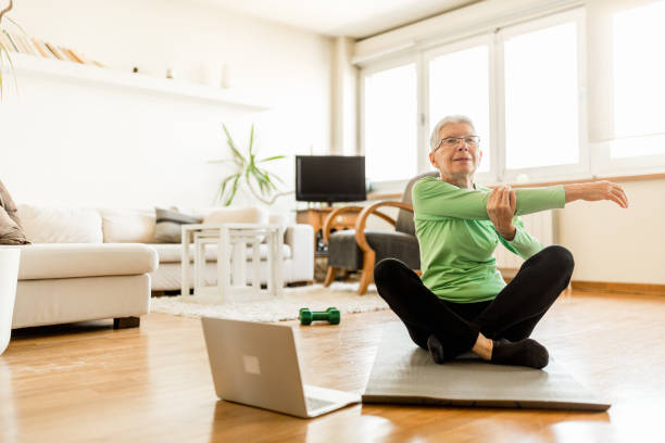 Active senior woman home exercising with online coach stock photo