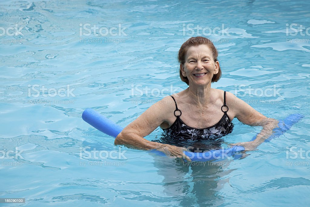 Active senior woman in swimming pool exercising with blue water stock photo