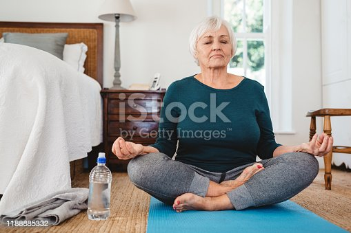 Active senior woman sitting on a mat on her bedroom floor meditating in the lotus pose while practicing yoga in the morning
