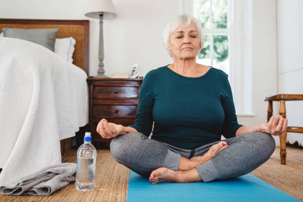 Active senior woman in the lotus pose while practicing yoga stock photo