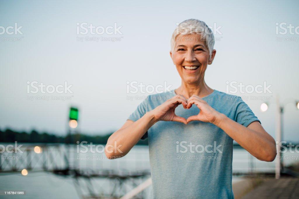 Actieve Senior vrouw het maken van een hart met haar handen - Royalty-free 60-69 jaar Stockfoto