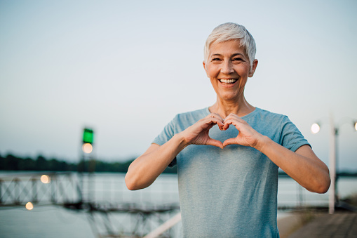 Portrait of a happy senior woman making a heart shape with her hands after exercising on the riverbank.