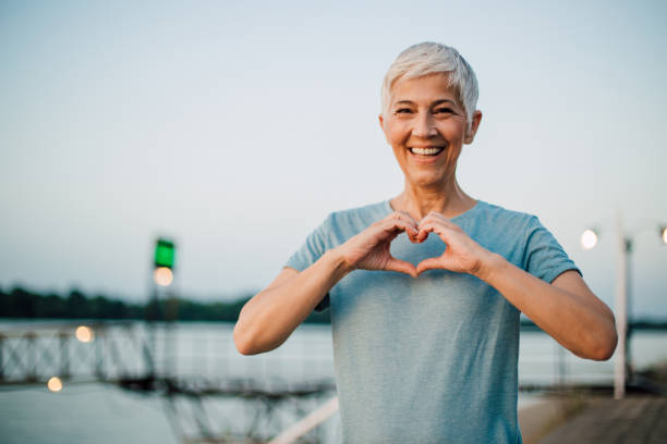 Active senior woman making a heart with her hands Portrait of a happy senior woman making a heart shape with her hands after exercising on the riverbank. wellbeing stock pictures, royalty-free photos & images