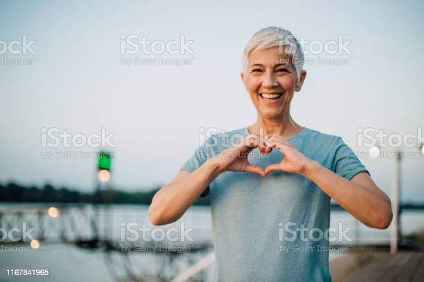 Actieve Senior Vrouw Het Maken Van Een Hart Met Haar Handen Stockfoto en meer beelden van 60-69 jaar