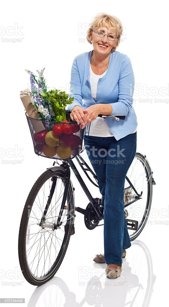 Active senior woman Portrait of smiling senior woman standing next to bicycle with grocery shopping in the basket. Studio shot, white background. 60-69 Years Stock Photo
