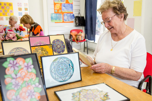istock Active Senior Woman Showing Hand Made Art Craft In The Community Center 650234052