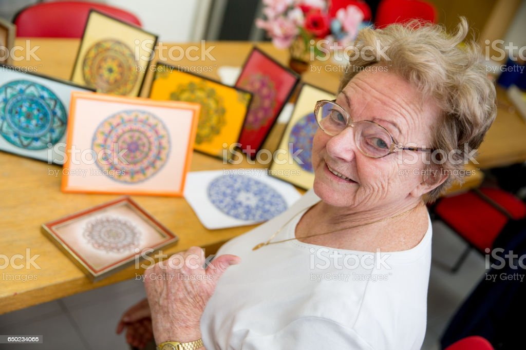 Active Senior Woman Showing Hand Made Art Craft In The Community Center stock photo