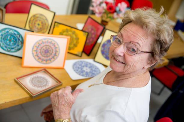 mujer senior activa mostrando hecho a mano artesanía en el centro de comunidad - clase de arte fotografías e imágenes de stock