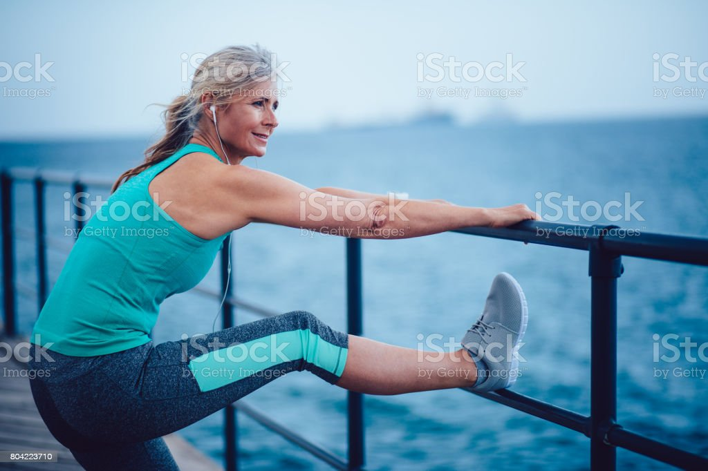 Active senior woman warming up by the sea for jogging stock photo