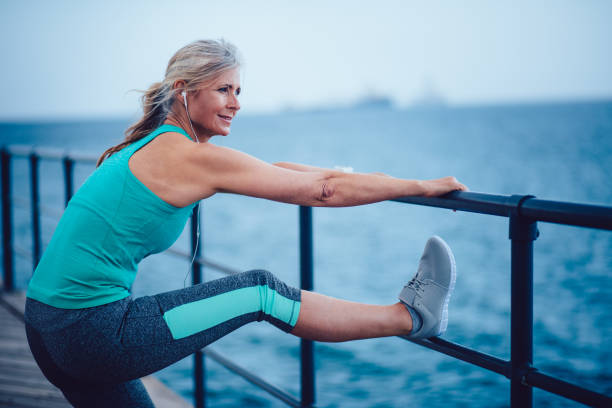 Active senior woman warming up by the sea for jogging Athletic mature woman in sportswear stretching her legs after morning jogging by the sea one mature woman only stock pictures, royalty-free photos & images
