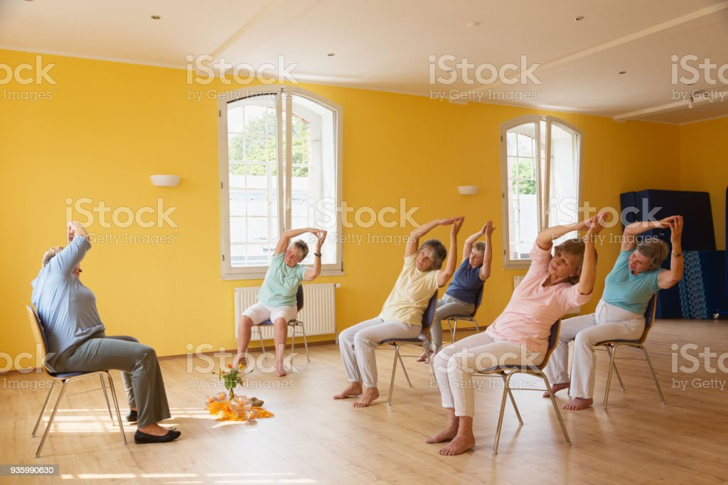 active senior women in yoga class exercisig on chairs, stock photo