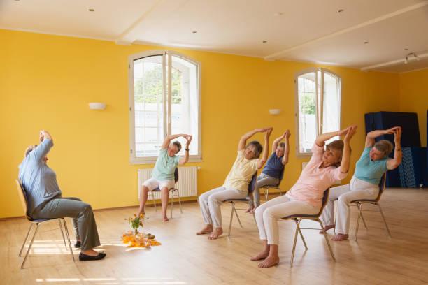active senior women in yoga class exercisig on chairs, - krzesło zdjęcia i obrazy z banku zdjęć