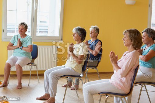 istock active senior women in yoga class exercisig on chairs 935990674
