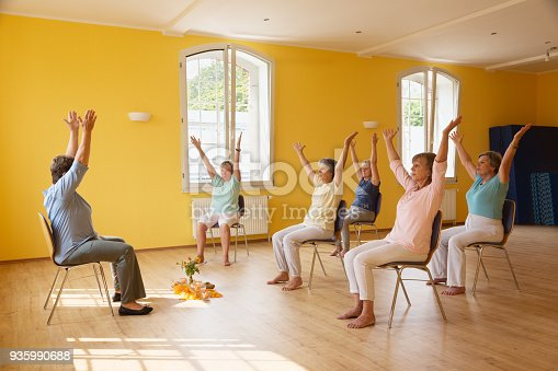 istock active senior women in yoga class exercisig on chairs 935990688