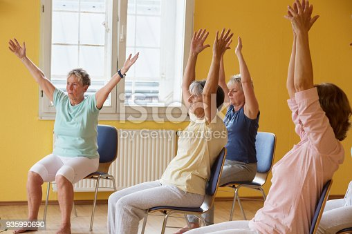 istock active senior women in yoga class exercisig on chairs 935990690