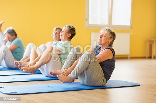 istock active senior women in yoga class exercising on mat and having fun 935993042