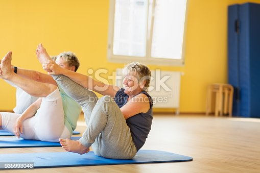 istock active senior women in yoga class exercising on mat and having fun 935993046