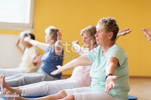 istock Active senior women in yoga class exercising on mat sitting 935993464