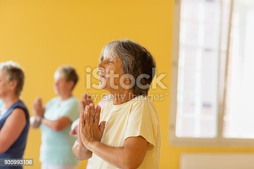 istock Active senior women in yoga class exercising standing in prayer pose, smiling 935993106
