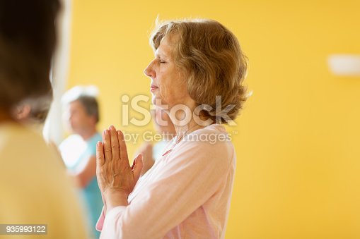 istock Active senior women in yoga class exercising standing in prayer pose 935993122