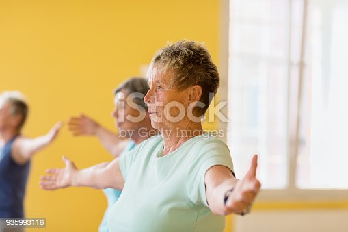 istock Active senior women in yoga class exercising standing with outstretched arms 935993116