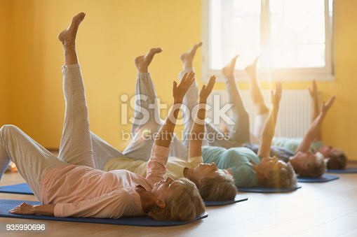 istock active senior women in yoga class lying on mat, arms and legs raised 935990696
