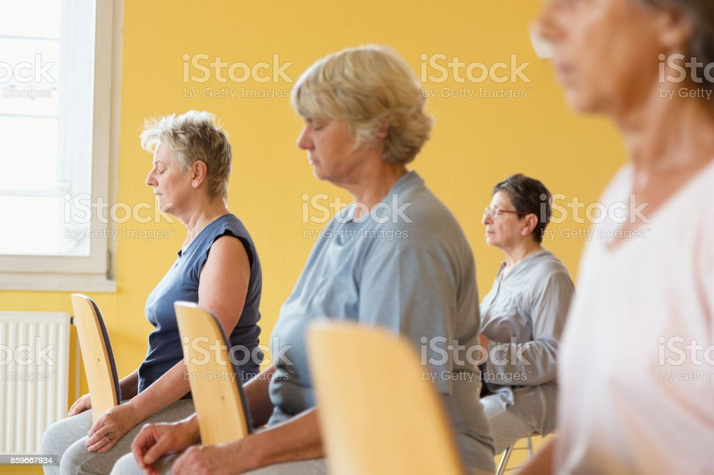 active senior women in yoga class on chairs, doing relaxation exercise stock photo