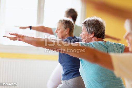 istock active senior women in yoga class warrior pose 935990670