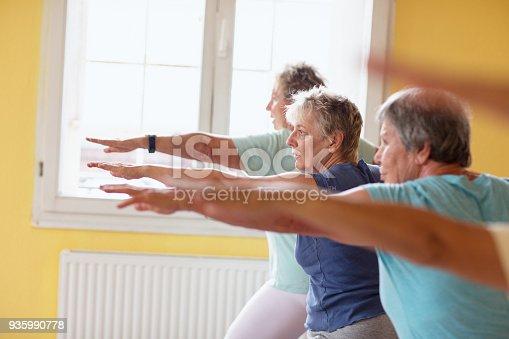 istock active senior women in yoga class warrior pose 935990778