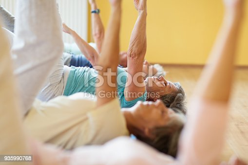 istock active senior women praciticing yoga lying on mat, arms raised 935990768