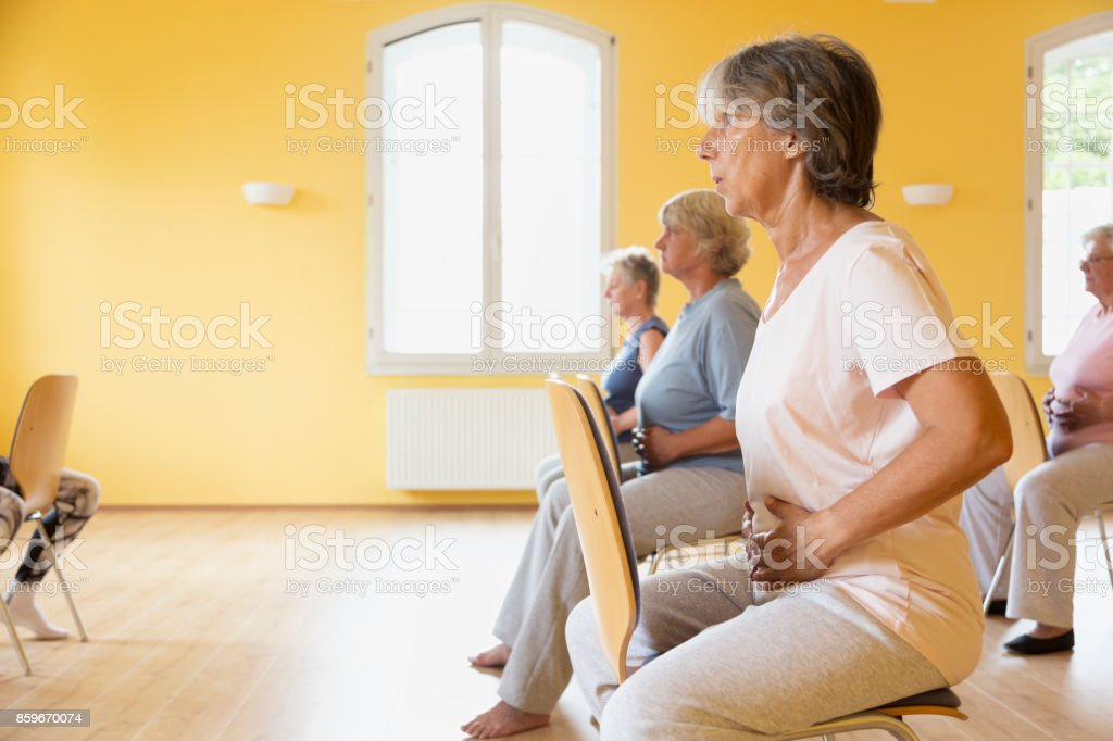 active senior women yoga class on chairs, doing breathing exercise stock photo