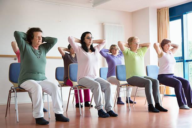 aktywny senior kobiety jogi na krzesła - krzesło zdjęcia i obrazy z banku zdjęć
