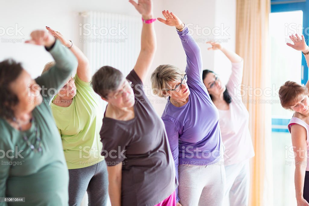 active senior women yoga class stock photo
