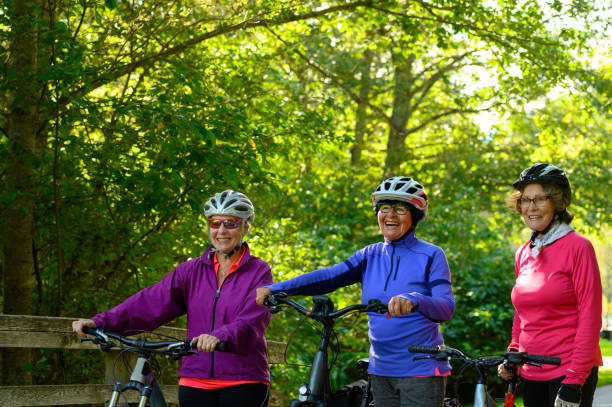 Active seniors bonding in the great outdoors Senior women cycling together. Active seniors living a healthy lifestyle. Staying active in retirement. ebike for elder stock pictures, royalty-free photos & images
