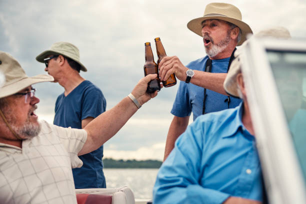active seniors brothers on a fishing trip on a boat. - older brother imagens e fotografias de stock