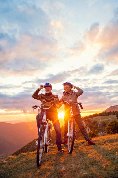 Active seniors having walk with bike in autumn nature. They having romantic time outdoor. stock photo