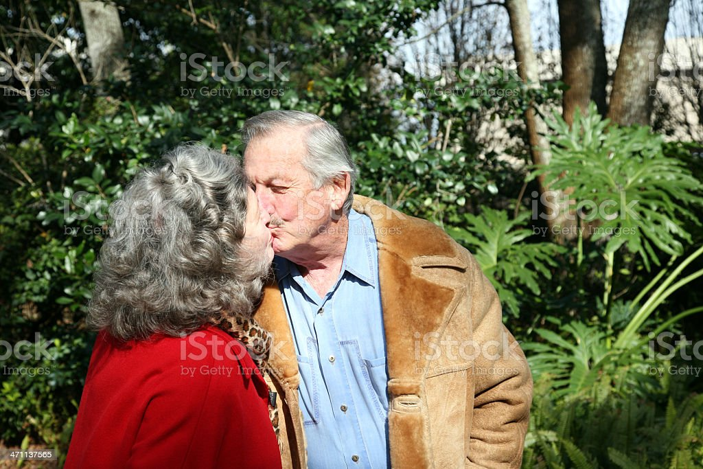 Active Seniors Kissing in Beautiful Garden royalty-free stock photo