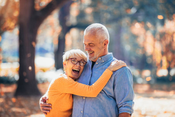 Active seniors on a walk in autumn forest stock photo