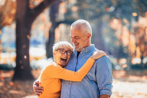 Los ancianos activos en un paseo en el bosque de otoño - foto de stock