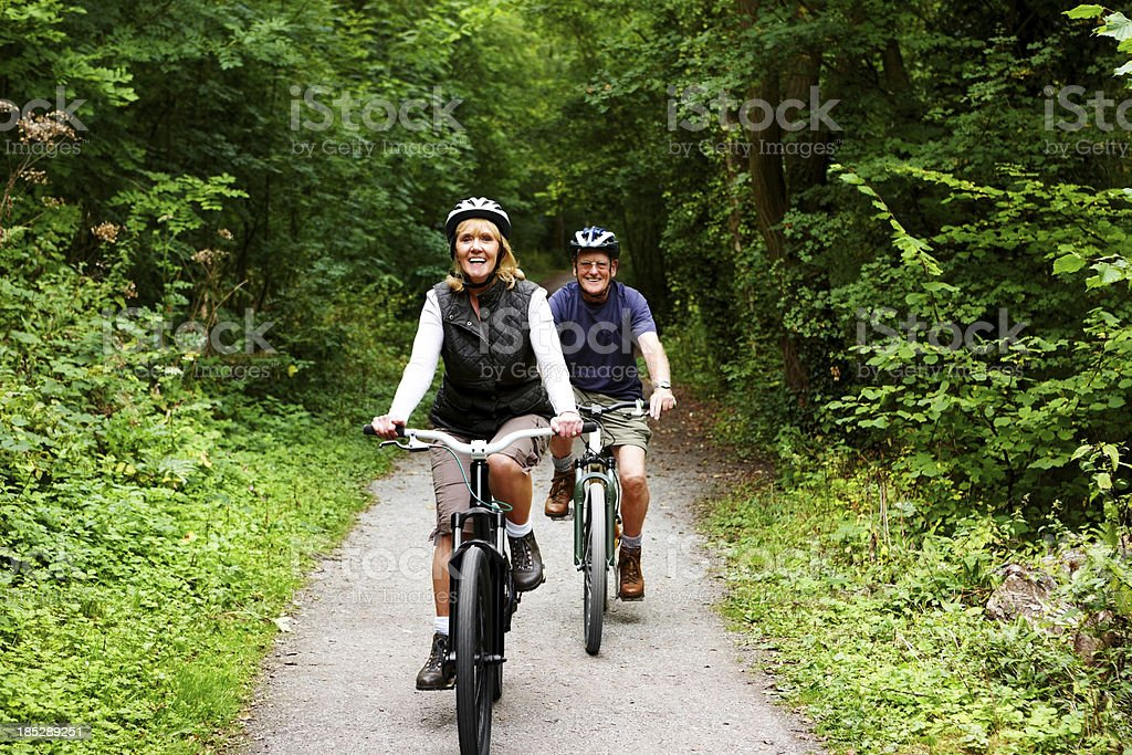 Active seniors riding bicycle in countryside royalty-free stock photo