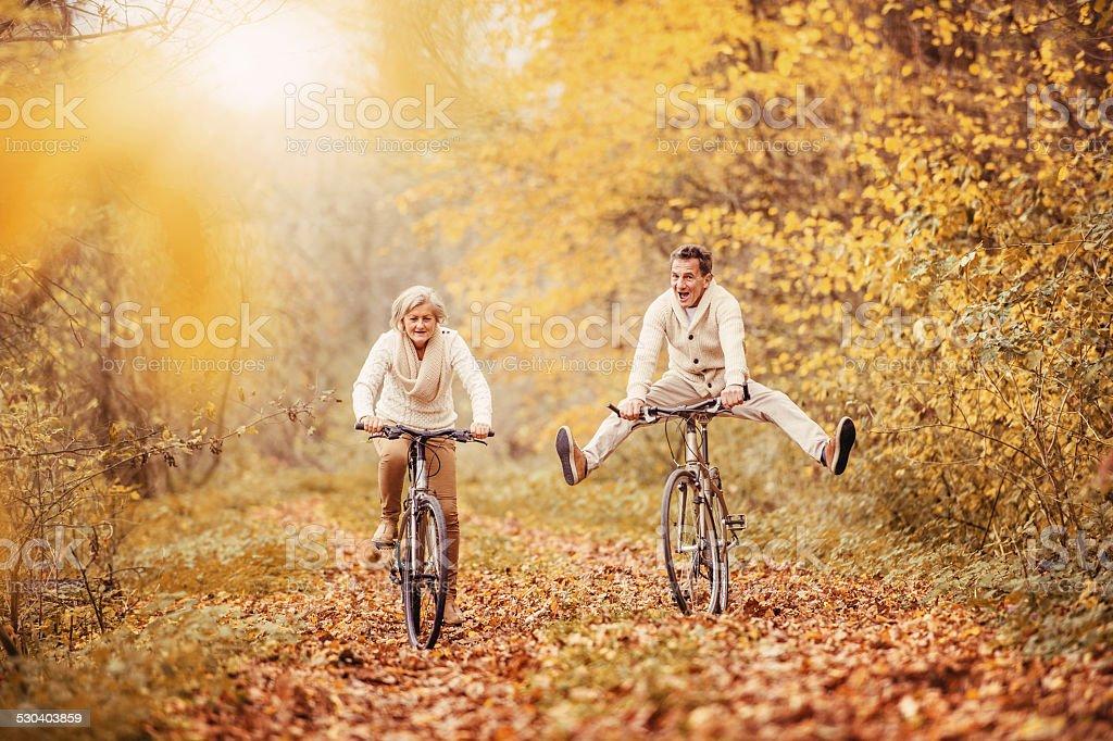 Active seniors riding bike and having fun stock photo