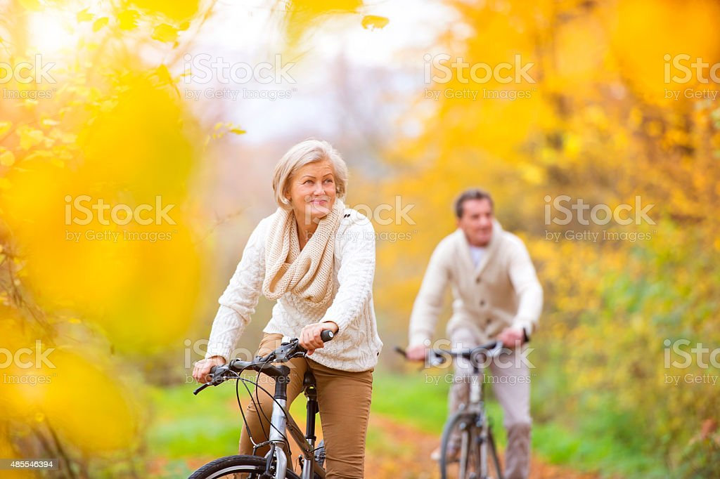 Active seniors riding bikes Active seniors riding bikes in autumn nature. They having romantic time outdoor. Autumn Stock Photo