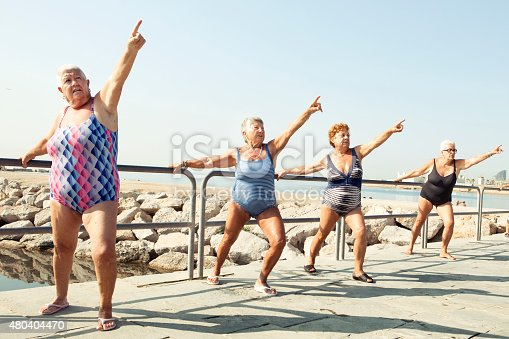 istock Active seniors stretching during outdoor fitness class 480404470