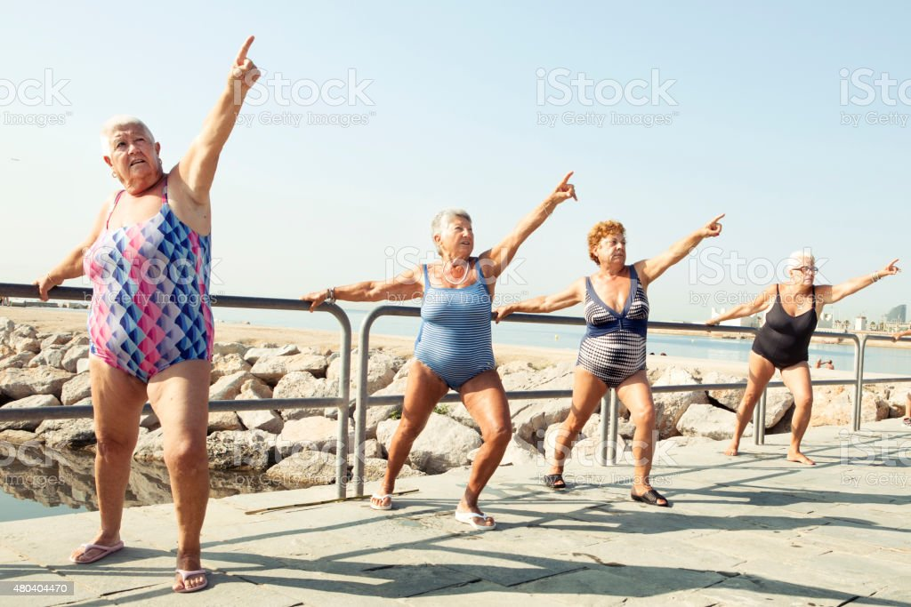 Active seniors stretching during outdoor fitness class stock photo